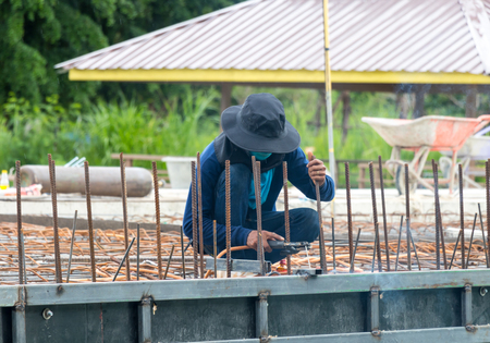 Construction workers are welding steel rods cement