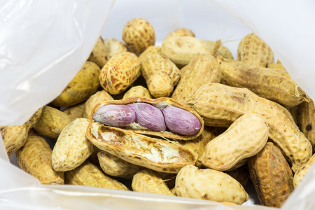 boiled peanuts on a pile of peas in plastic bag ready to eat Stock Photo