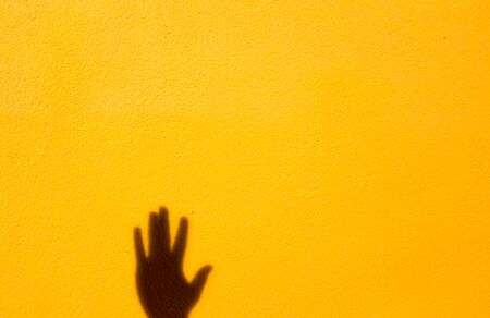 Shadow of the left hand on the yellow wall concept for your design