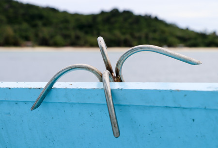 grapnel in a traditional wooden boat on the sea with island background Stock Photo