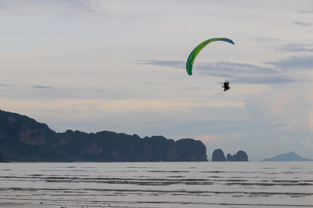 Paramotor is flying over the beach in the evening