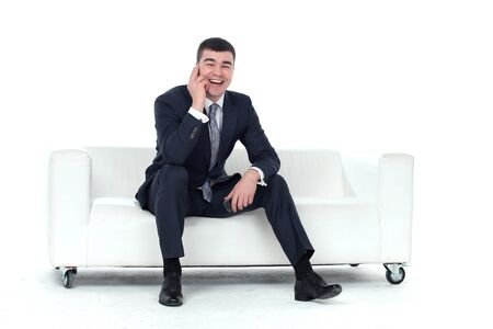 full suit: Young man talking on the phone sitting on a sofa isolated on white background Stock Photo