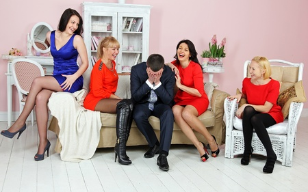 Four young women and a young man sitting in a room and laugh Stock Photo - 12746616