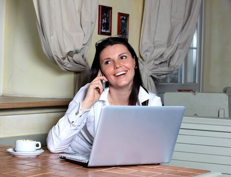 Young attractive business woman working on her laptop and talking on the phone in a cafe Stock Photo - 12746381