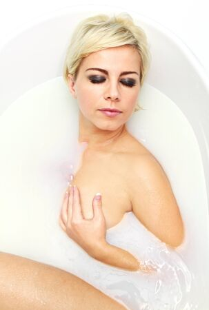 young woman lying in the bath with milk photo