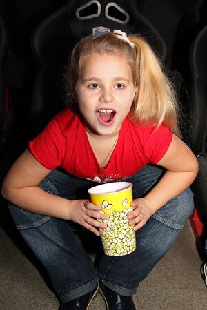 little girl sitting on armchairs at cinema photo