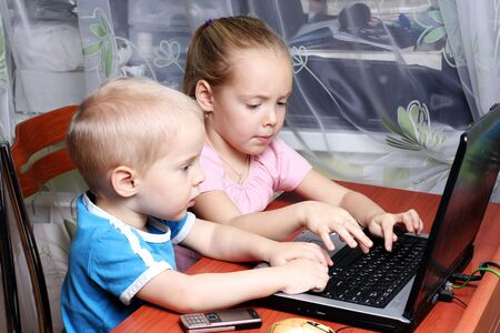 Boy and girl working together on a laptop photo