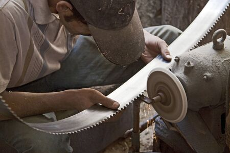 Sharpening saw blades in wood carving workshop, Hotan, Xinjiang, China  Stock Photo