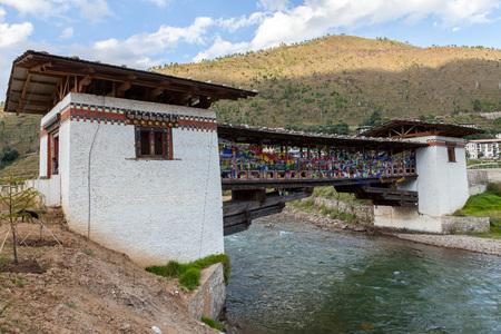 Bridge with prayer flags over Wang Chhu river in Thimphu, Bhutan photo