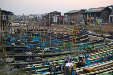 Sunset and unidentified, colorful long wooden boats for tourists at pier in Nyaungshwe, Myanmar , 28 of feb. 2015 Editorial
