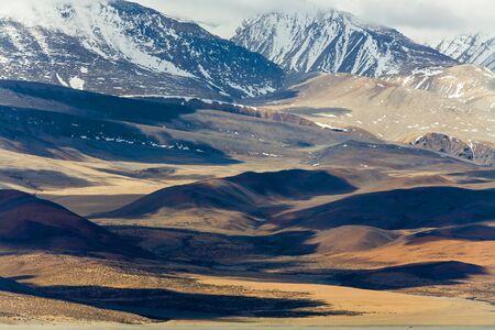 Dark cloud over Tibetan hillsides beyond Lake Manasarovar, Tibet, China.