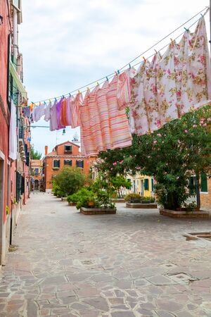 Colorful  building facades along  tranquil canals in Murano island,  Venice, Italy.
