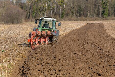 Farmer in tractor plowing field.
