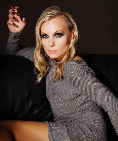 Belle jeune femme assise sur un canapé, fumant un cigare