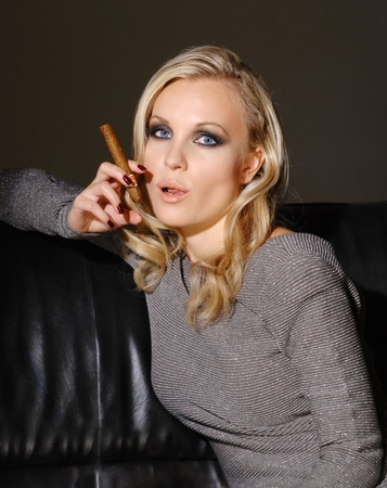 Beautiful  young  lady sitting on a sofa, smoking a cigar