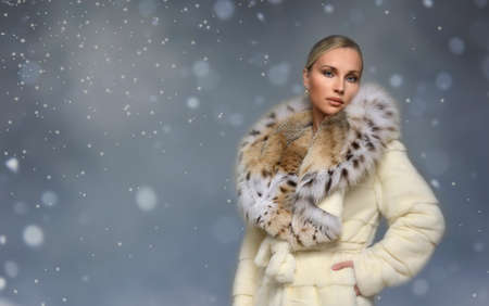 Beautiful woman wearing luxury white lynx fur coat. Winter fashion model. Snow background.