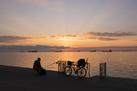 Fisherman sillhouette at city sunset with bicycle. Thessaloniki, Greece Stock Photo