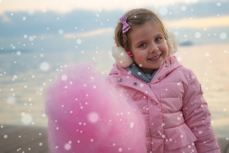 Sweet smiling little girl with Pink Cotton candy smiling outdoors