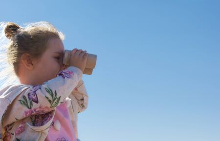 smiling little girl looking through binocular. Eco concept