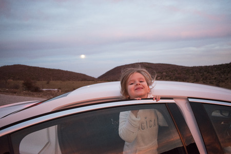 Happy travel concept. Adorable little girl goes on vacation by car. Sunset on the mountain road