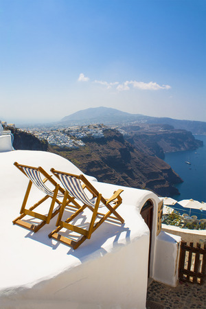 Two sunbeds on the terrace with sea view. Relax on Santorini island, Greece.