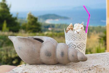 Summer coctail fresh concept idea. Sea shells coctail on the summer beach landscape background.