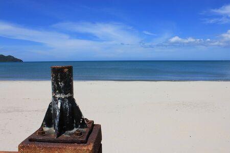 brighten: electricity post base standing alone on beach in brighten atmosphere