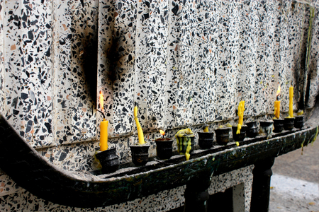 piety: The altar melted candle yellow color on candlestick in Thai temple Buddha Asia Stock Photo