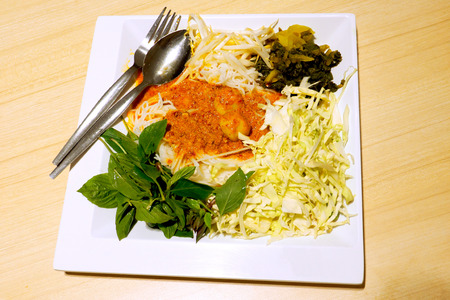 Khanom chin is noodles with fish curry coconut milk or served with a hot and spicy fish-based sauce. Thai food in white plate on wood desk Stock Photo