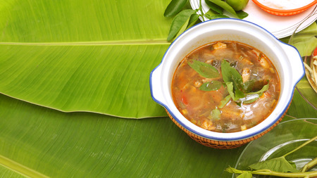 favorite soup: Spicy pork neck grilled Soup background Thai Isan favorite herbal green food for diet control have eat with noodle vegetable lemon,Thai morning glory all on banana leaf and left area for your word.