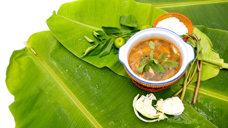 favorite soup: Spicy pork neck grilled Soup background Thai Isan favorite herbal green food for diet control have eat with noodle vegetable lemon,Thai morning glory all on banana leaf and free space for your word.