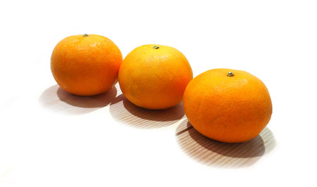availability: Three Orange balls on a pine table have shadow two layer on white background isolate.