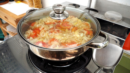 lass: Egg with onion and tomato soup boiling in a stainless steel pot  have a lass lid and cooking on the gas stove, Photo focus select at egg and vegetables middle left. The menu is healthy and delicious, Very easy to made. Stock Photo