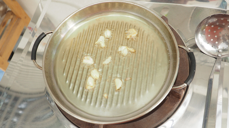 first step: Garlic fried cooking with palm oil is first step, In stainless still pan on LPG gas stove. Stock Photo