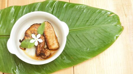 Marinated pork with garlic and pepper sauce For one person to eat Adorned with flowers heal the white area. White ceramic bowl Place on a banana leaf green and wood, Concept nature See more appealing and refreshing and has space for your word. Stock Photo