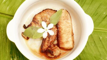 Marinated pork with garlic and pepper sauce For one person to eat Adorned with flowers heal the white area. White ceramic bowl Place on a banana leaf green Concept nature See more appealing and refreshing.