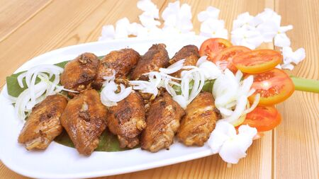 Marinated chicken wings fried has decorate are onions, tomato on the banana leaf in plate and background is canna flower. Stock Photo