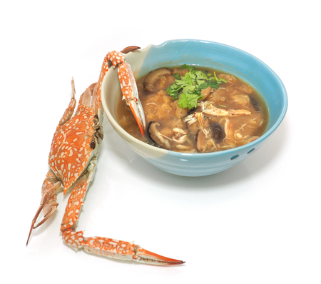 Braised fish maw in red gravy abalone mushroom with crab meat, The presentation of the more interesting and difference on with teamed crabs trying to use the pincers fork over of food in the bowl on white background. Stock Photo