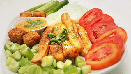 French fries with Thousand Island salad sauce served with vegetable are appetizers, meatballs, fish tofu, cucumber, tomatoes; onion, coriander sliced, Photo close up full frame see the detail.