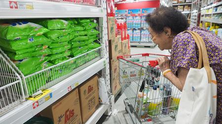 Grangmom (my mother) see the washing powder price and pushing a shopping cart at Makro Sainoy branch Bangbuathong provice Thailand Asia 17 October 2017 01:00 PM. Editöryel