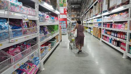 Grandma (my mother) looking the washing powder and pushing a shopping cart at Makro Sainoy branch Bangbuathong provice Thailand Asia 17 October 2017 01:00 PM.