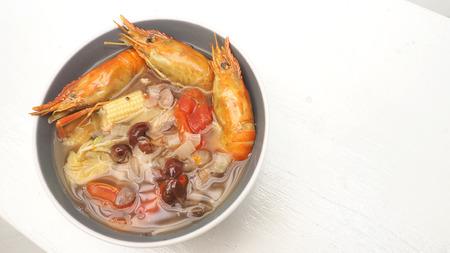 Suki Giant malaysian prawn menu idea on white wood has copy space, The ingredients are red grapes, onion, tomato, baby Corn, Enoki Mushroom.