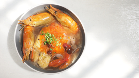 Giant malaysian prawn pour the sauce chili sweet and sour diet and health menu idea on white wood has copy space, The ingredients are red grapes, onion, tomato, baby Corn, Chinese cabbage, Enoki Mushroom and pumpkin soup.