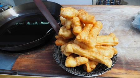 Deep fried dough stick in sieve long handle on vintage wood desk kios shop at Yoawarach Bangkok Thailand, Close up photo.