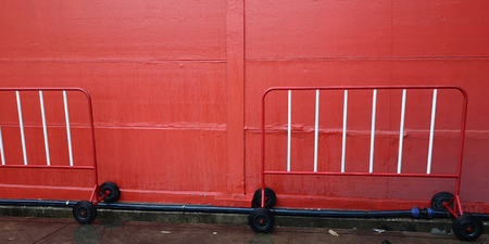 Background texture has traffic barrier red and white color and HDPE pipe, conduit hardware tools.