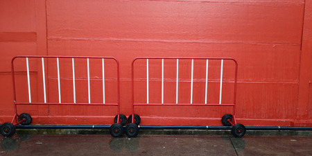 Background texture red and white color has traffic barrier a font of the wall with 2 traffic barrier. Stock Photo