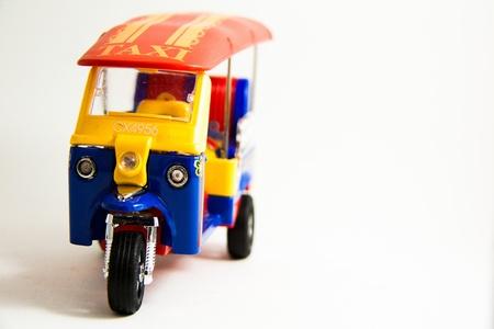 tuktuk: Font Taxi Thailand tuktuk model red blue yellow colors on white background - Thai souvenirs