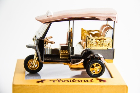 Tuktuk Model Taxi Thailand gold and copper color on yellow box print Thailand on white background - Thai souvenirs Stock Photo