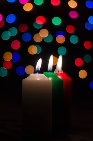 3 candles with colorful bokeh in the dark background  photo