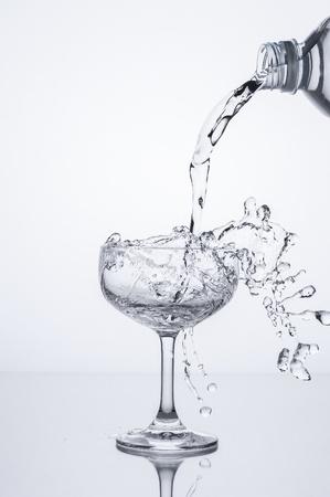 gieten van water in glas Stockfoto